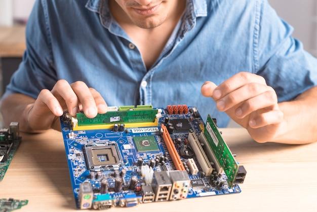 Obenliegende ansicht des männlichen technikers it, der motherboard repariert