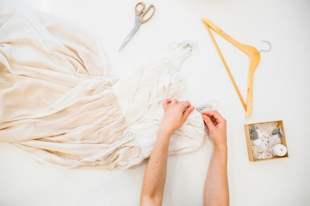 Obenliegende ansicht des nähenden kleides der modedesigner hand