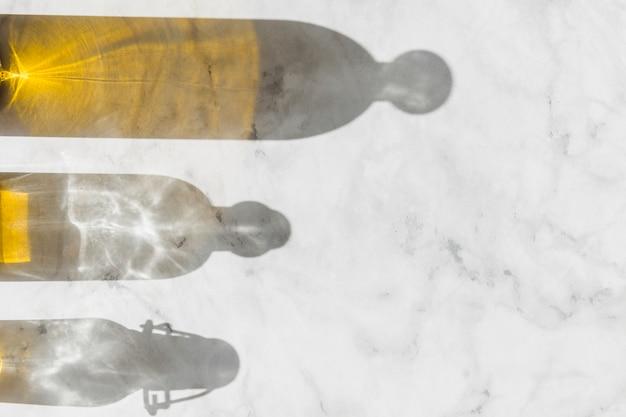 Obenliegende ansicht des olivenflaschenschattens auf weißem boden
