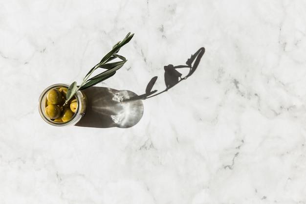 Obenliegende ansicht des olivenglases mit dem zweig auf marmorhintergrund