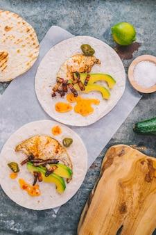 Obenliegende ansicht des omeletts mit avocado auf tortilla