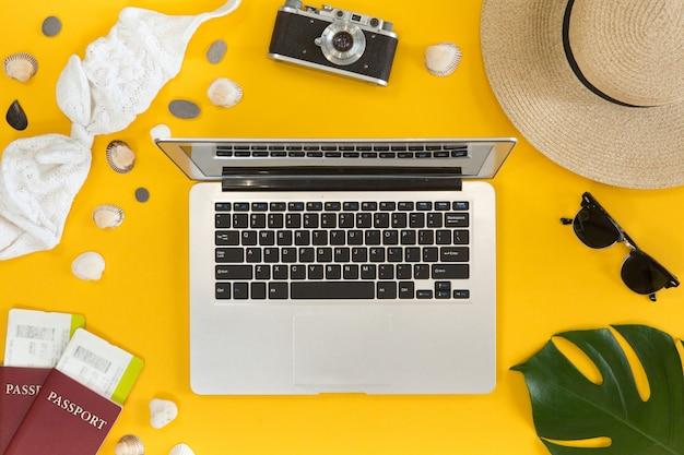 Obenliegende ansicht des on-line-reisekonzeptes. draufsicht des laptop-, pass-, flugtickets-, laptop- und reisendzubehörs, reisebürogeschäftskonzept.