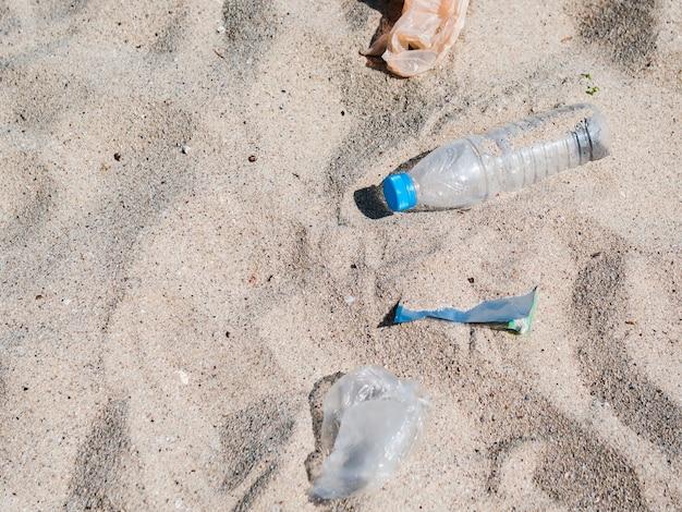 Obenliegende ansicht des plastikabfalls auf sand am strand