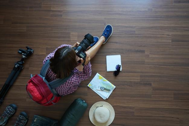 Obenliegende ansicht des reisendenfrauenplanes und -rucksacks mit dem halten der kamera