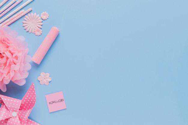 Obenliegende ansicht des rosa handwerkskunst- und -hausarbeitstextpapiers auf blauem hintergrund