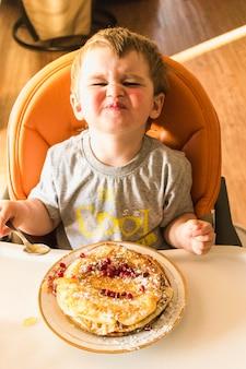 Obenliegende ansicht des schmollenden babys beim pfannkuchen essend
