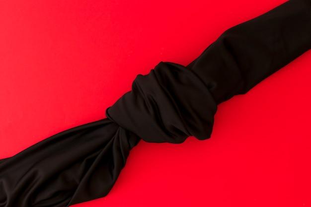Obenliegende ansicht des schwarzen knotengewebes auf rotem hintergrund