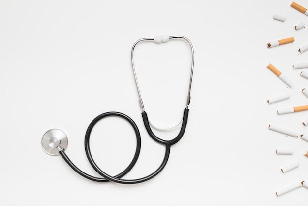 Obenliegende ansicht des stethoskops und der defekten zigaretten über weißem hintergrund