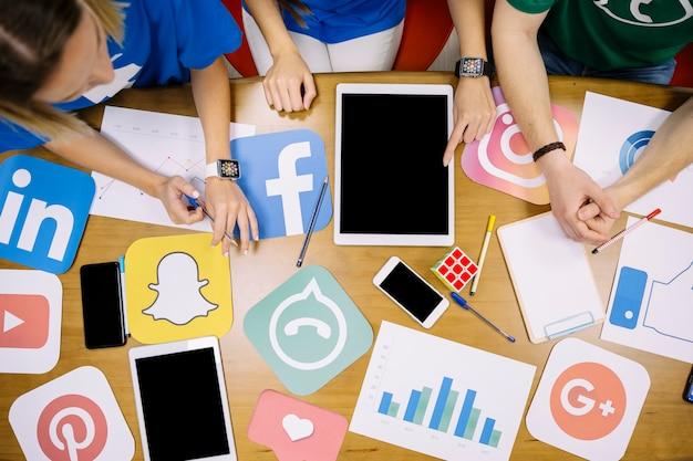 Obenliegende ansicht des teams, das an social media-anwendungen arbeitet