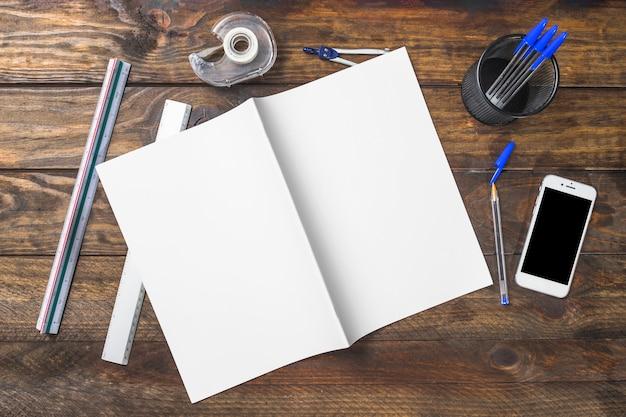 Obenliegende ansicht des weißbuches mit schreibwaren und des mobiltelefons auf hölzernem hintergrund
