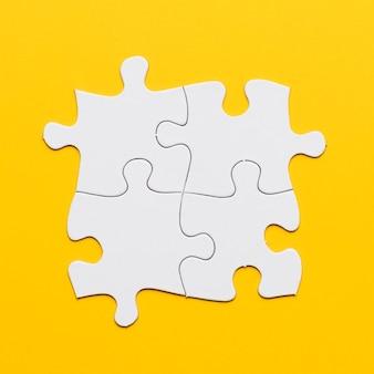 Obenliegende ansicht des weißen gemeinsamen puzzlespiels auf gelbem hintergrund