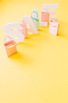 Obenliegende ansicht des weißen verkaufswortes mit kleinen rosa einkaufstaschen auf gelbem hintergrund