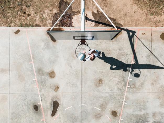 Obenliegende ansicht des werfenden balls des mannes im basketball