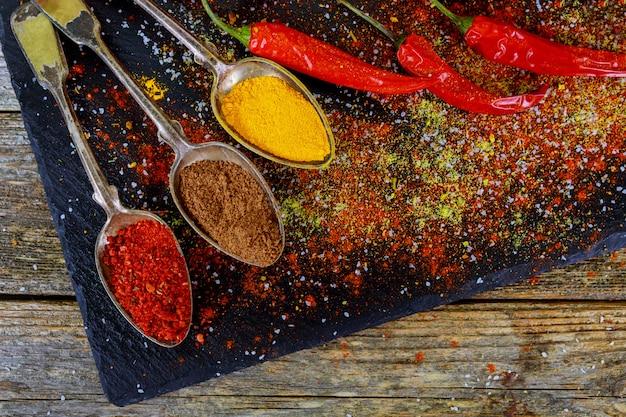 Obenliegende ansicht, die das kochen mit gewürzen in einer rustikalen küche mit schüsseln buntem grundgewürz darstellt