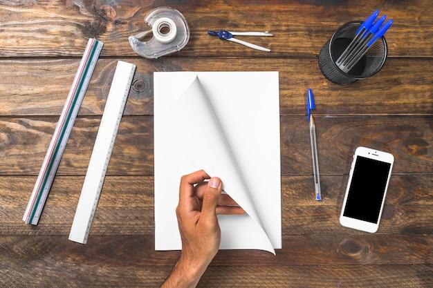 Obenliegende ansicht einer person, die seite mit briefpapier und handy auf tabelle dreht