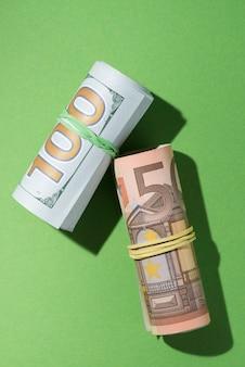 Obenliegende ansicht von aufgerollten banknoten auf grünem hintergrund