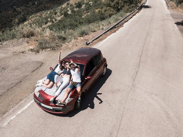 Obenliegende ansicht von den freunden, die auf der autohaube sitzt, die selbstporträt nimmt