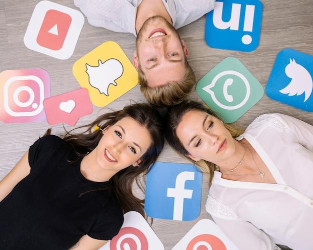 Obenliegende ansicht von den freunden, die auf hintergrund mit social media-ikonen liegen