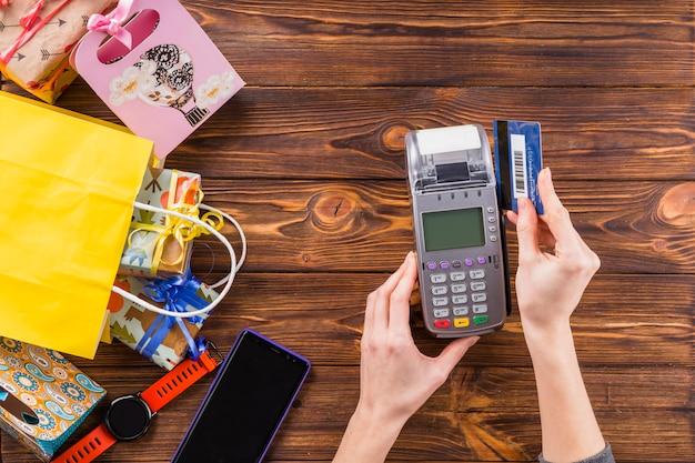 Obenliegende ansicht von den händen, die kreditkarte durch zahlungsanschlußgerät auf holzoberfläche klauen