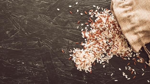 Obenliegende ansicht von den mischreiskörnern, die vom sack überlaufen