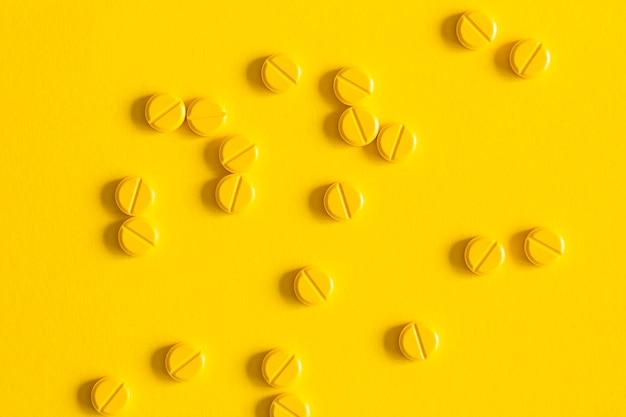 Obenliegende ansicht von den pillen zerstreut über den gelben hintergrund