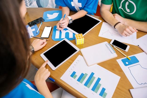 Obenliegende ansicht von den talentierten leuten, die digitale tablette am arbeitsplatz verwenden