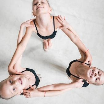Obenliegende ansicht von drei ballerinamädchen, die schulter jedes anderen oben schauen anhalten