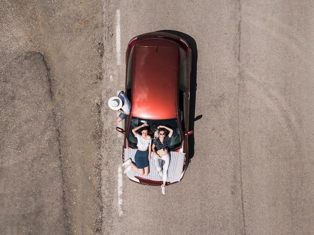 Obenliegende ansicht von freunden mit auto auf straße