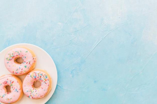 Obenliegende ansicht von frischen rosa donuts auf platte