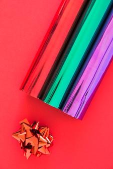 Obenliegende ansicht von glitterverpackungspapieren und -bogen auf rotem hintergrund