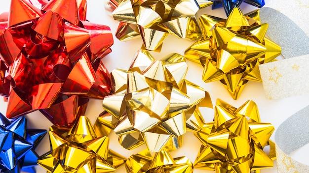 Obenliegende ansicht von goldenem; rote und blaue dekorative bänder auf weißem hintergrund