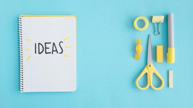 Obenliegende ansicht von ideentext auf notizbuch mit stationärem auf blauem hintergrund