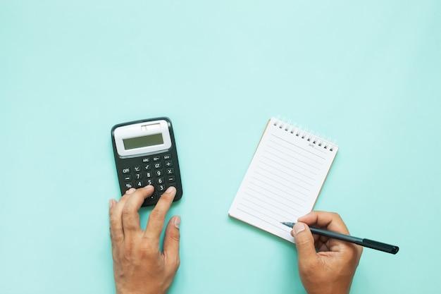 Obenliegende ansicht von mannhänden unter verwendung der taschenrechner- und papieranmerkung über blauen farbhintergrund mit kopienraum