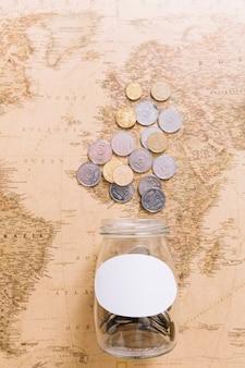 Obenliegende ansicht von münzen und von einem offenen glas auf weltkarte
