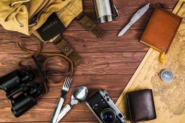 Obenliegende ansicht von reisenden ausrüstungen über hölzernem schreibtisch