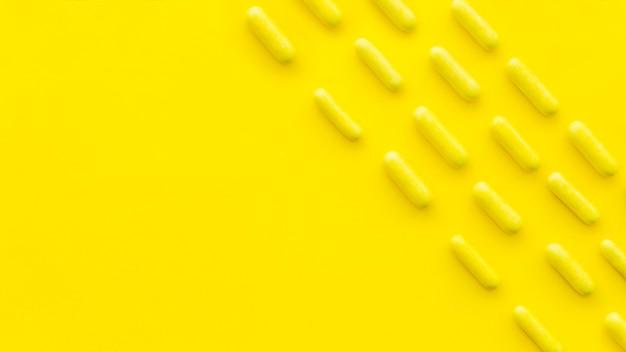 Obenliegende ansicht von süßigkeitskapseln in folge auf gelbem hintergrund