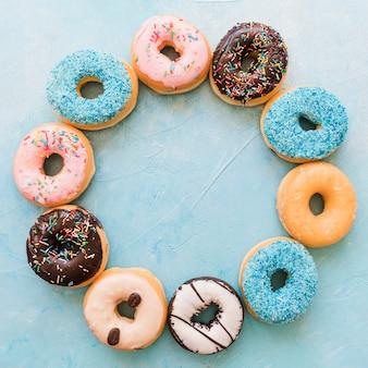 Obenliegende ansicht von verschiedenen frischen donuts, die kreisrahmen bilden