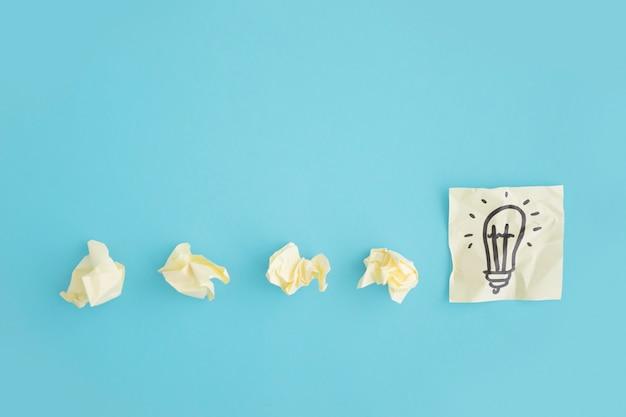 Obenliegende ansicht von zerknitterten papieren mit glühlampe zeichnen auf die klebrige anmerkung über dem blauen hintergrund