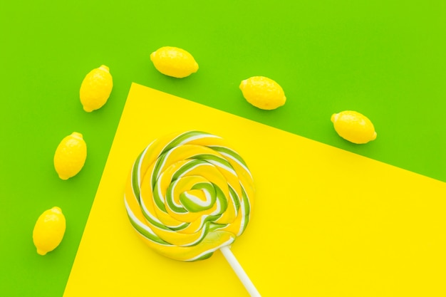 Obenliegende ansicht von zitronensüßigkeiten und -lutscher auf dem doppelten gelben und grünen hintergrund