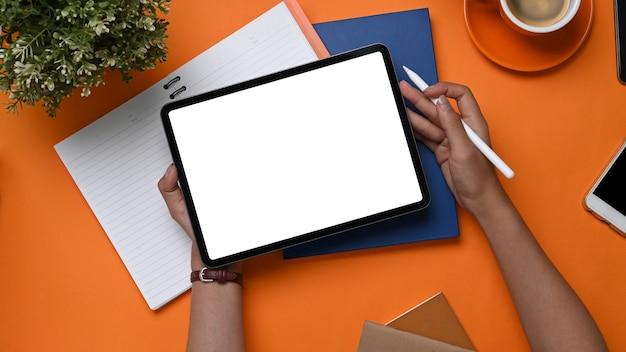 Obenliegende aufnahme der jungen designerin, die digitale tablette und stylus-stift auf orangem hintergrund hält.