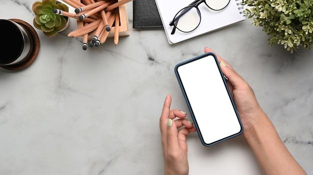 Obenliegende aufnahme einer frau, die ein smartphone mit weißem bildschirm auf marmorhintergrund hält.