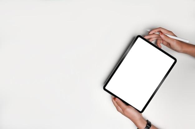 Obenliegende frau, die mock-up digitales tablet und stylus-stift auf whithintergrund hält.