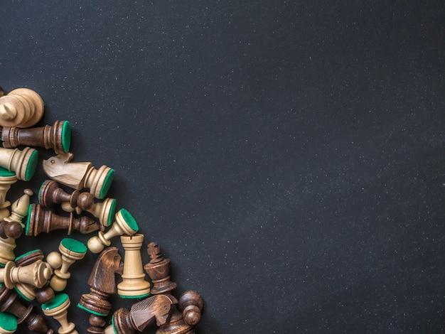 Obenliegende klassische hölzerne schachfiguren auf dunklem tabellenkopienraum