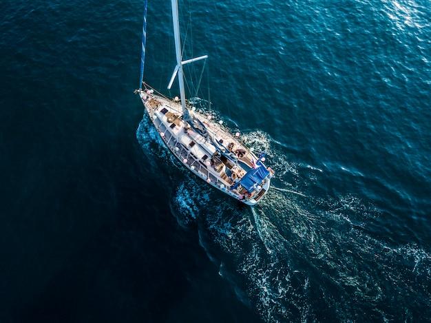 Obenliegende spitzenvogelperspektive des luxussegelbootes in der haarscharfen blauen meerwasserlagune