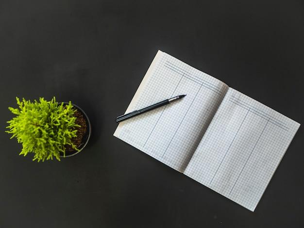 Obenliegender geöffneter leerer wortschatz mit stift auf schwarzer tabelle mit blume
