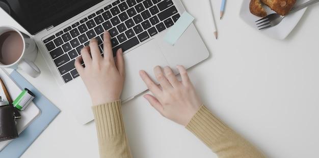 Obenliegender schuss der jungen frau schreibend auf laptop-computer im bequemen arbeitsplatz