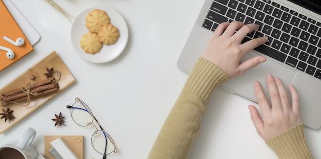 Obenliegender schuss der jungen frau schreibend auf laptop-computer im herbstarbeitsplatz