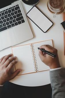 Obenliegender schuss des berufsgeschäftsmannes sein ideenkonzept auf notizbuch beim arbeiten schreibend mit laptop