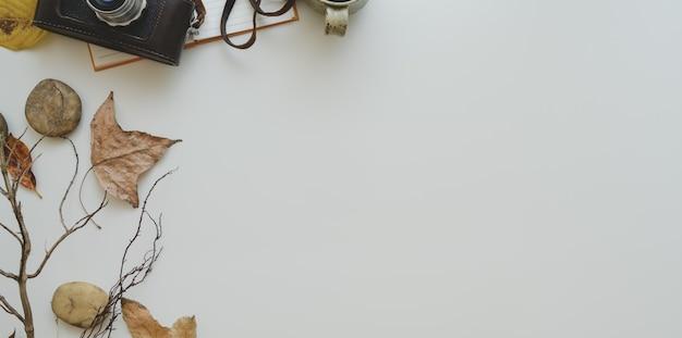 Obenliegender schuss des minimalen arbeitsplatzes mit herbstlaub und kopienraum mit büroartikel