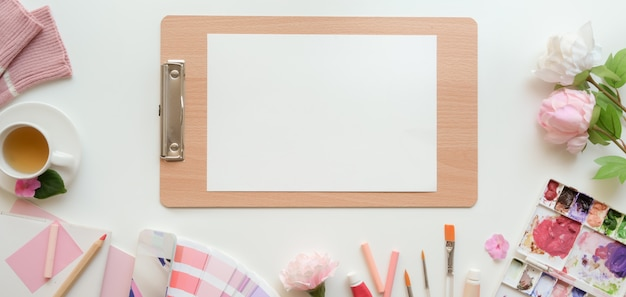 Obenliegender schuss des rosa weiblichen künstlerarbeitsplatzes mit skizzenpapier und malwerkzeugen